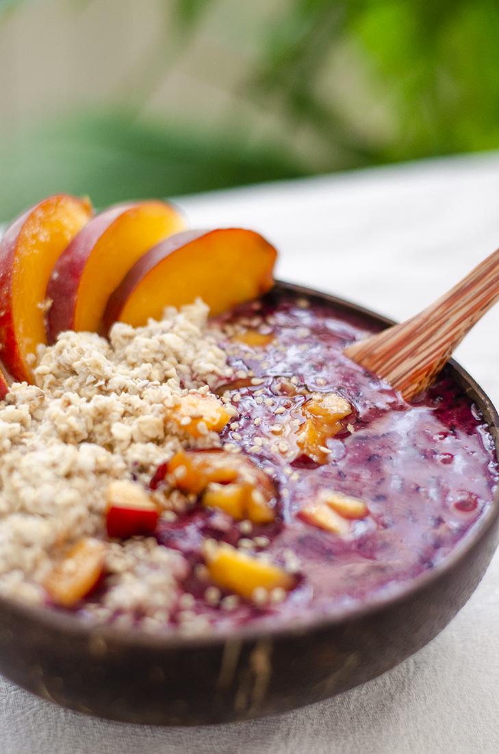 Coconut bowl de avena y helado casero de arándanos con rodajas de melocotón. Un desayuno vegano fácil, rápido y barato.