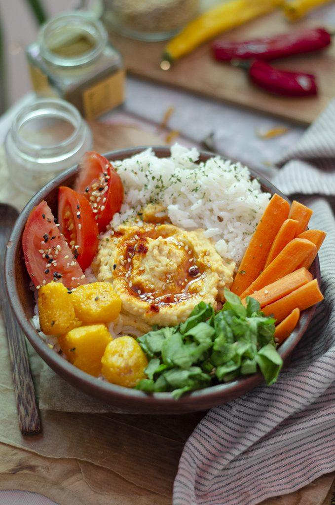 Bowl saludable de arroz, hummus casero, crudités y calabaza